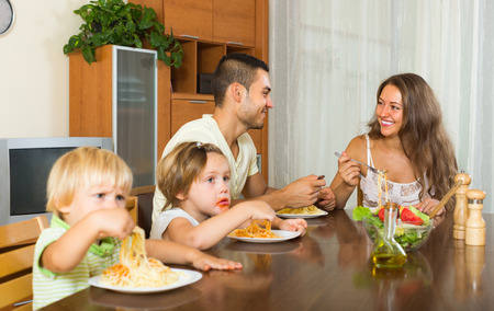 gladful: Happy young family of four eating with spaghetti at table