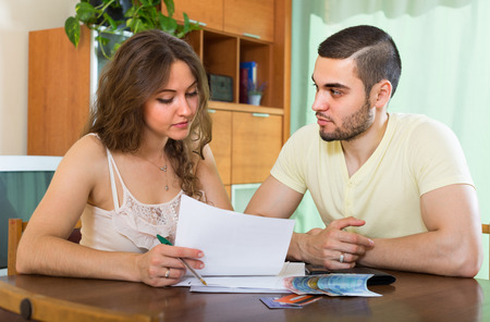 Young couple sitting at the table and calculating the family budget photo