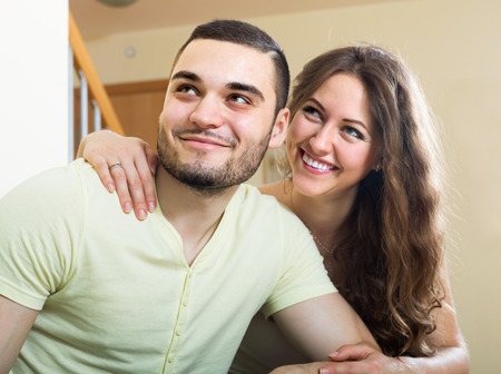 gladful: Happy smiling young couple sitting on sofa in living room