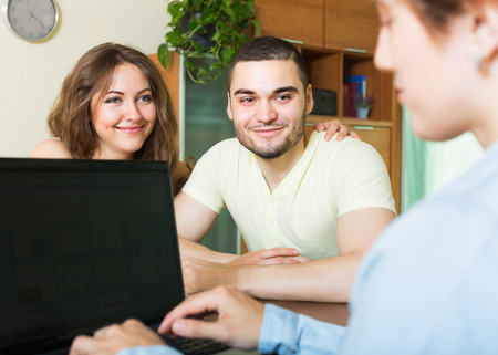 private insurance: Positive couple discussing details of private insurance with agent