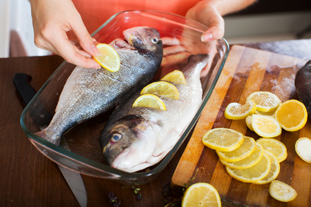 fryingpan: Close-up of housewife putting pieces of lemon in fish at  kitchen