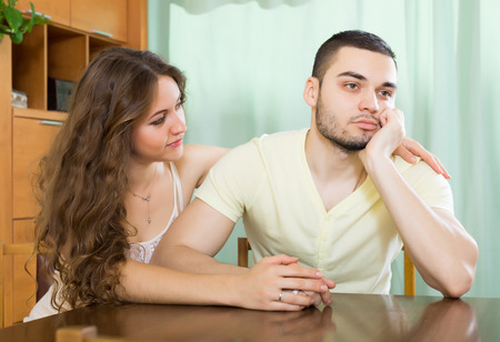 to reassure: Loving woman consoling the depressed man  at table
