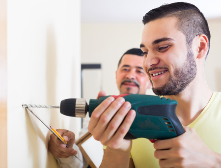 Young smiling son and mature father drilling wall indoors photo