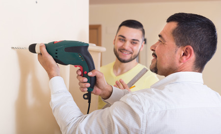 two level house: Two male adults with drill and level in house Stock Photo