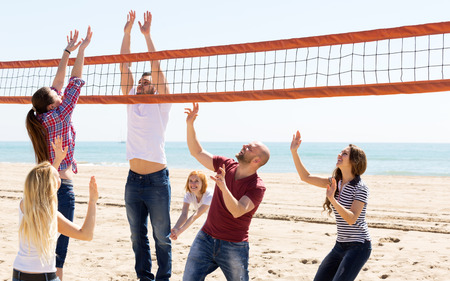 positive adults throwing ball over net and laughing. Focus on the right pair photo