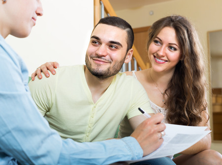 private insurance: Smiling young couple discussing details of private insurance with agent