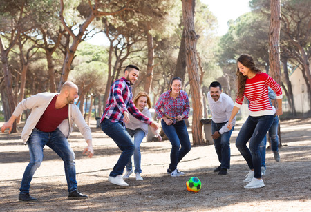 freetime activity: Happy active adult friends playing football at picnic lunch. Selective focus