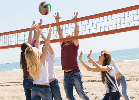 Heated friends playing volleyball at sandy beach photo
