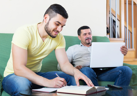 Mature professor giving private lesson to positive student at home photo
