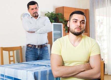 odds: Portrait of two negative male adults being at odds indoors