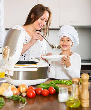 Happy mother and little daughter cooking healthy food in  multicooker at kitchen photo