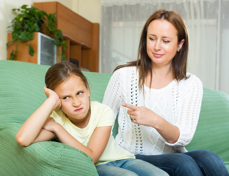 lament: adult woman scolding crying child at  home interior . Focus on girl Stock Photo