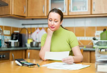 penury: Satisfied female looking through bills at kitchen Stock Photo
