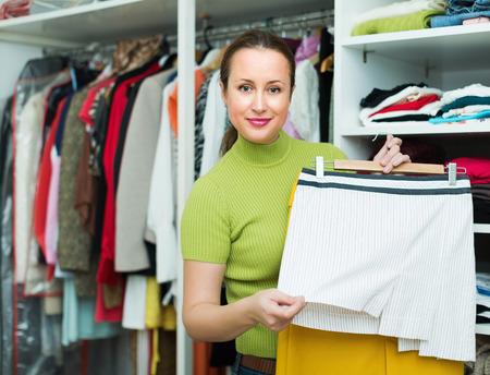 ordelijk: Ordelijke gelukkige huisvrouw regelen kleren op kleerkast indoor