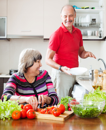 doing chores: happy elderly man and mature woman  doing chores together in the kitchen
