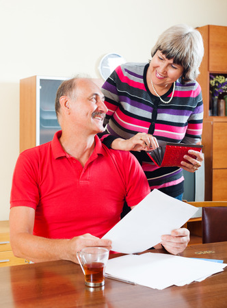 50 something fifty something: Happy mature family  with financial documents at home interior Stock Photo