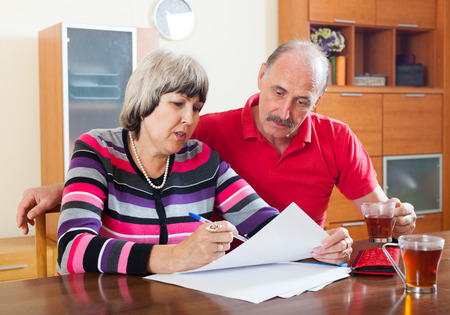 calculated: serious mature couple reading financial document together at home Stock Photo