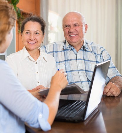 outreach: Happy mature couple answer questions of outreach worker with laptop in  home