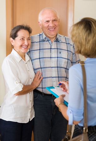 Mature couple 60-70 years old  answering the questions of young employee  in door at home