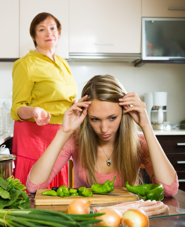 fracas: Adult daughter and mature mother having conflict  in home kitchen