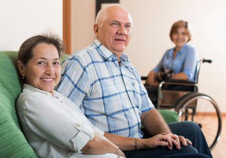 Älteres Paar und behinderten Mädchen auf Stuhl zu Hause