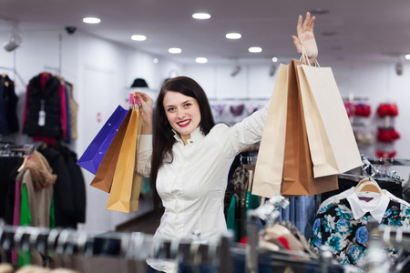 gladful: Young female buyer with bags at clothing store Stock Photo