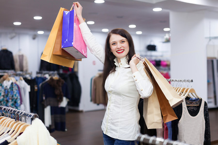 gladful: Portrait of cute woman with shopping bags at fashionable store