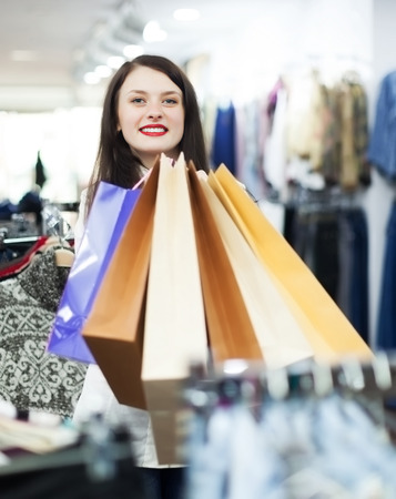 gladful: Happy girl with shopping bags at clothing store