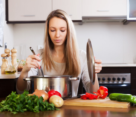 ordinary woman: Ordinary  woman  with ladle cooking soup Stock Photo