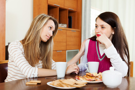 home comforts: crying woman has problem, other woman  consoling her at table in home Stock Photo