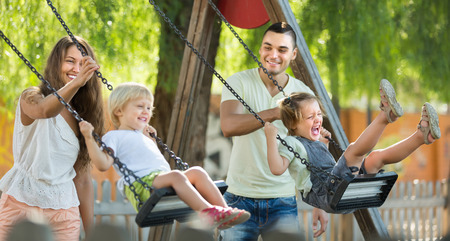 Happy young cheerful family of four at playgrounds swings. Focus on woman