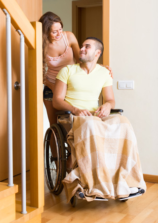 coming home: Smiling young woman and her disabled husband in wheelchair coming home Stock Photo