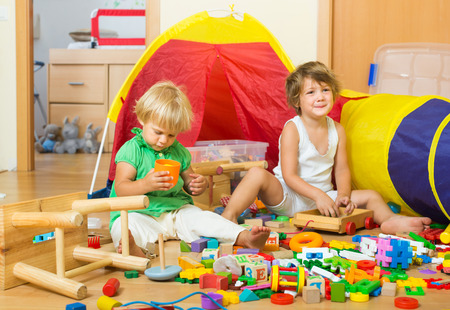 3 4 years: Two siblings playing with toys together indoor. Selective focus on one girl Stock Photo