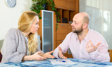 covetous: Serious man and woman with financial documents at home