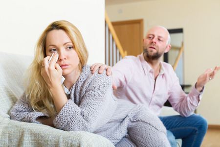 consoling: Man consoling the depressed young woman on sofa at home. Focus on girl Stock Photo