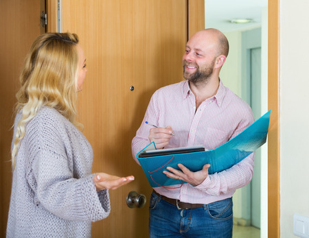 conducting: Blonde woman answer questions of outreach worker with paper in home door