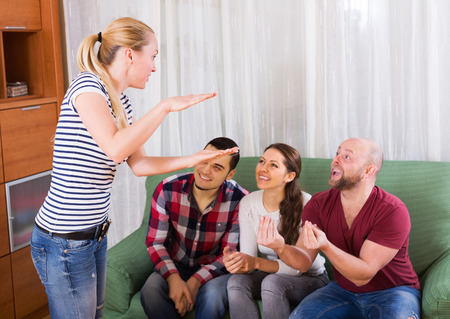 Group of cheerful young adults having fun at house booze party