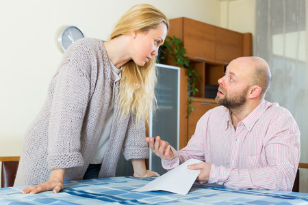 covetous: Young unpleased couple having conflict over financial documents at home Stock Photo
