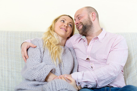 gladful: Happy couple in love at home in the living room sitting on sofa. Focus on woman Stock Photo