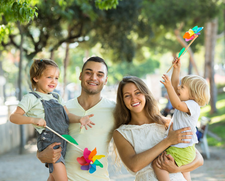 fun activity: Cheerful young parents holding kids with toy windmills at summer day Stock Photo