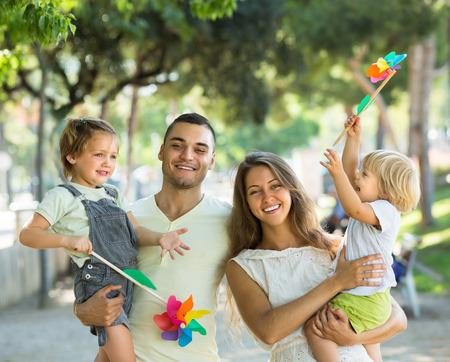 familia feliz casa: Los padres jóvenes alegres que llevan a cabo los niños con los molinos de viento de juguete en día de verano Foto de archivo