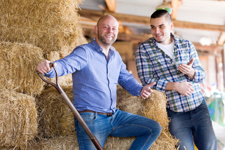hayloft: Portrait two smiling farm workers working in the hayloft. Focus on the left man