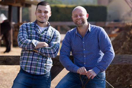 woodshed: Two positive smiling male farmers standing with spades at farmyard
