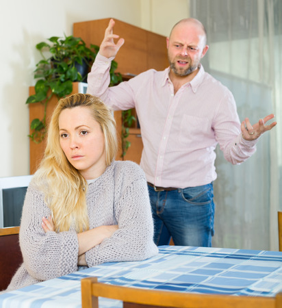 jackboot: Angry man and young sad woman having quarrel at home