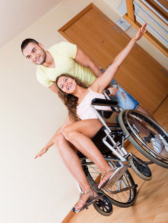 invalidity: Happy couple with smiling spouse who sitting on wheelchair in playful mood Stock Photo
