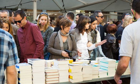 decided: BARCELONA, SPAIN - APRIL 23, 2015:  Books on street stalls  in Barcelona. Saint George is saint patron of city, decided to give red roses and books Editorial