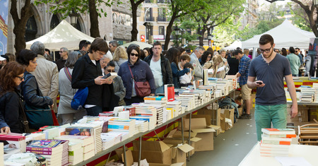 catalunia: BARCELONA, SPAIN - APRIL 23, 2015:  Books on street stalls in Barcelona, Catalonia. Books and red roses - symbols of Sant Jordi feast in Catalunia
