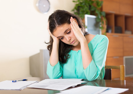 poorness: Crying woman reading  documents at her home Stock Photo