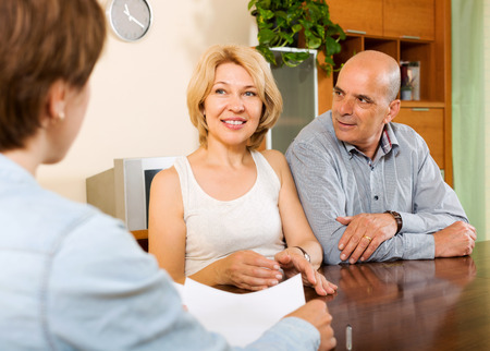 agent: Mature  couple discussing details of private insurance with agent Stock Photo