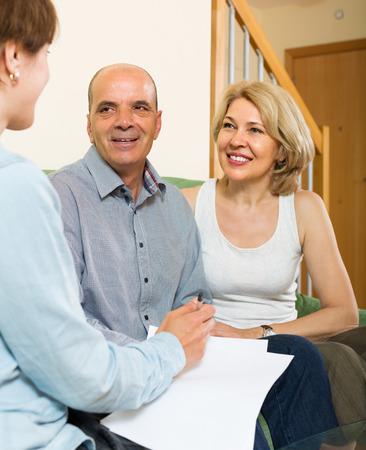 empleada domestica: Sonreír cuestionario llenado pareja madura para los empleados en la sala de estar